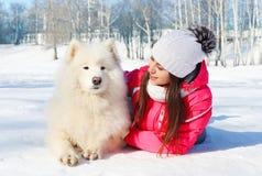 Dueño de la mujer del retrato con el perro blanco del samoyedo que miente el invierno de la nieve Foto de archivo libre de regalías