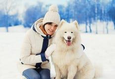Dueño de la mujer que abraza el perro blanco del samoyedo en nieve en invierno Foto de archivo