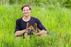 Dueño feliz que acaricia su perro Pastor alemán que miente en la hierba Fotografía de archivo