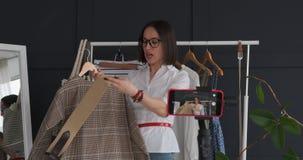Dueño femenino del boutique que registra un vídeo sobre el nuevos vestido y accesorio almacen de video