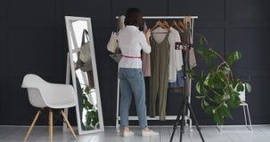 Dueño femenino del boutique vlogging sobre el nuevos vestido y accesorio almacen de metraje de vídeo