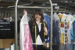 Dueño femenino que sostiene el vestido limpio en lavadero Fotos de archivo libres de regalías