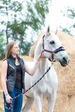 Dueño joven del adolescente que se coloca cerca de su caballo blanco Foto de archivo