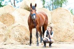 Dueño joven del adolescente que se sienta cerca de su caballo de bahía Imagen de archivo