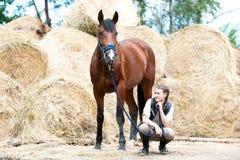 Dueño joven del adolescente que se sienta cerca de su caballo de bahía Imagen de archivo libre de regalías
