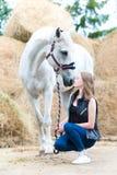 Dueño joven del adolescente que se sienta cerca de su caballo blanco Imagen de archivo libre de regalías