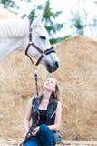 Dueño joven del adolescente que se sienta cerca de su caballo blanco Foto de archivo