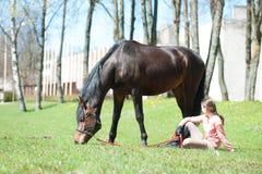 Dueño joven del adolescente que se sienta cerca de su caballo preferido Fotos de archivo libres de regalías