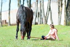 Dueño joven del adolescente que se sienta cerca de su caballo preferido Imagen de archivo