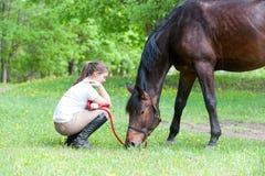 Dueño joven del adolescente que se sienta cerca de su caballo preferido Foto de archivo