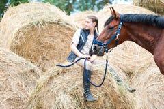 Dueño joven del adolescente que se sienta cerca de su caballo rojo Imagenes de archivo