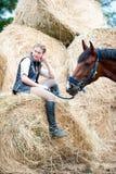Dueño joven del adolescente que se sienta cerca de su caballo rojo Foto de archivo libre de regalías