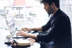 Dueño maduro de un negocio en un programa negro de la camisa para los dispositivos digitales usando la conexión libre 4G Imágenes de archivo libres de regalías