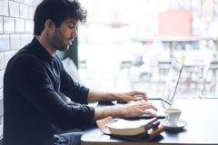 Dueño maduro de un negocio en una camisa negra que pone al día el programa para los dispositivos digitales usando la conexión lib Imagen de archivo libre de regalías