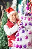 Dueño que adorna el árbol de navidad con las bolas Foto de archivo