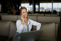 Dueño sonriente de la mujer que habla en el teléfono móvil con el cliente mientras que se sienta con el ordenador portátil en su  Fotos de archivo