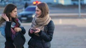 Due abbastanza giovani donne affascinanti alla moda che restano sul parcheggio, parlanti, ridenti e spillanti il telefono, camma  stock footage