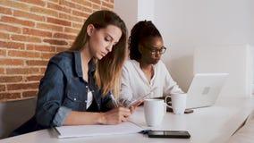 Due abbastanza giovani donne di affari che lavorano con la compressa digitale ed il computer portatile nell'ufficio stock footage