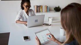 Due abbastanza giovani donne di affari che lavorano con la compressa digitale ed il computer portatile nell'ufficio archivi video