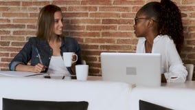 Due abbastanza giovani donne di affari che parlano e che bevono caffè mentre prendere per irrompere l'ufficio stock footage