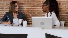 Due abbastanza giovani donne di affari che parlano e che bevono caffè mentre prendere per irrompere l'ufficio archivi video