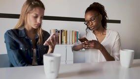 Due abbastanza giovani donne di affari facendo uso dei loro telefoni cellulari nell'ufficio stock footage