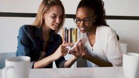 Due abbastanza giovani donne di affari facendo uso del suo telefono cellulare insieme mentre prendere irrompere l'ufficio video d archivio