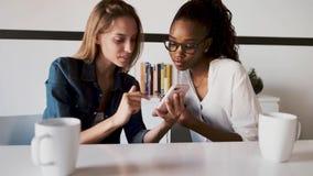 Due abbastanza giovani donne di affari facendo uso del suo telefono cellulare insieme mentre prendere irrompere l'ufficio archivi video