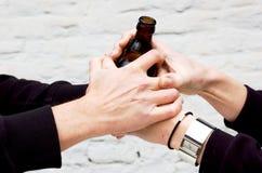 Due accoppiamenti delle mani che tengono un vetro scuro fotografia stock libera da diritti