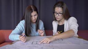Due achitects femminili lavorano al piano di bevelopment della città nel loro ufficio archivi video