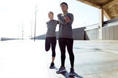 Due adatti e giovani donne sportive che fanno allungamento nella città Immagini Stock