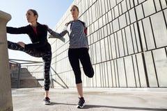 Due adatti e giovani donne sportive che fanno allungamento nella città Immagini Stock Libere da Diritti