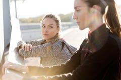 Due adatti e giovani donne sportive che fanno allungamento nella città Immagine Stock Libera da Diritti
