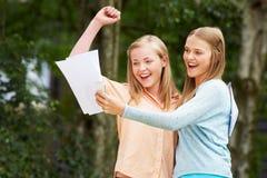 Due adolescenti che celebrano i riusciti risultati dell'esame immagini stock