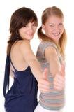 Due adolescenti che mostrano i pollici in su. fotografia stock
