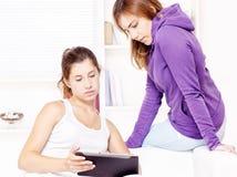 Due adolescenti che per mezzo del calcolatore del ridurre in pani Fotografia Stock