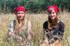 Due adolescenti che si siedono nel campo di grano Fotografie Stock