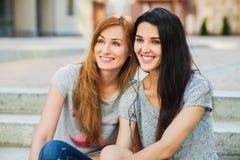 Due adolescenti che si siedono sulle scale e sulla musica d'ascolto Immagine Stock