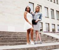 Due adolescenti davanti alla costruzione dell'università che sorridono, avendo Immagini Stock