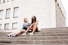 Due adolescenti davanti alla costruzione dell'università che sorridono, avendo Immagini Stock Libere da Diritti