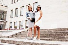 Due adolescenti davanti alla costruzione dell'università che sorridono, avendo Immagine Stock