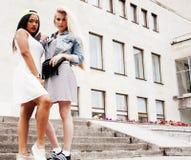 Due adolescenti davanti alla costruzione dell'università che sorridono, avendo Fotografia Stock Libera da Diritti