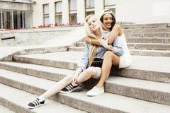 Due adolescenti davanti alla costruzione dell'università che sorridono, divertendosi, concetto della gente di stile di vita Fotografia Stock