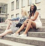 Due adolescenti davanti alla costruzione dell'università che sorridono, divertendosi, concetto della gente di stile di vita Immagini Stock