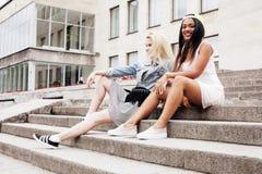 Due adolescenti davanti alla costruzione dell'università che sorridono, divertendosi, concetto della gente di stile di vita Immagini Stock Libere da Diritti