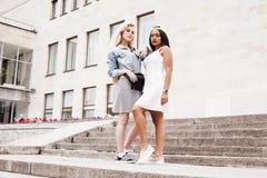 Due adolescenti davanti alla costruzione dell'università che sorridono, divertendosi, concetto della gente di stile di vita Immagine Stock Libera da Diritti