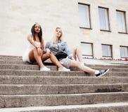 Due adolescenti davanti alla costruzione dell'università che sorridono, divertendosi Europa di viaggio, concetto della gente di s Immagine Stock