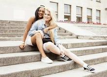 Due adolescenti davanti alla costruzione dell'università che sorridono, divertendosi Europa di viaggio, concetto della gente di s Fotografie Stock