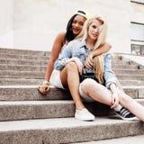 Due adolescenti di diversità davanti alla costruzione dell'università che sorridono, divertendosi, concetto della gente di stile  Fotografia Stock Libera da Diritti