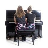 Due adolescenti e pianoforte verticale nero fotografia stock libera da diritti